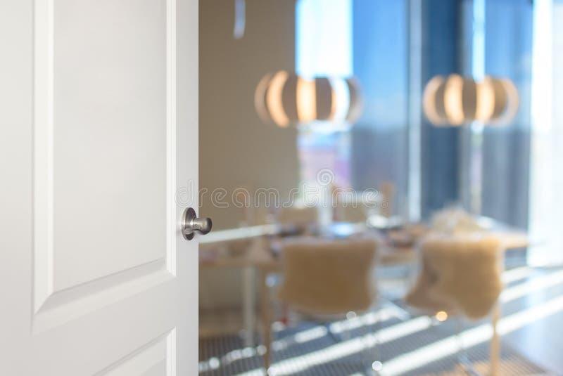 Άσπρη πόρτα που ανοίγουν στη τραπεζαρία, θολωμένο υπόβαθρο στοκ εικόνα