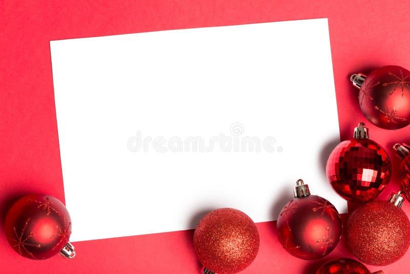 Άσπρη σελίδα με τα κόκκινα μπιχλιμπίδια Χριστουγέννων στοκ εικόνες