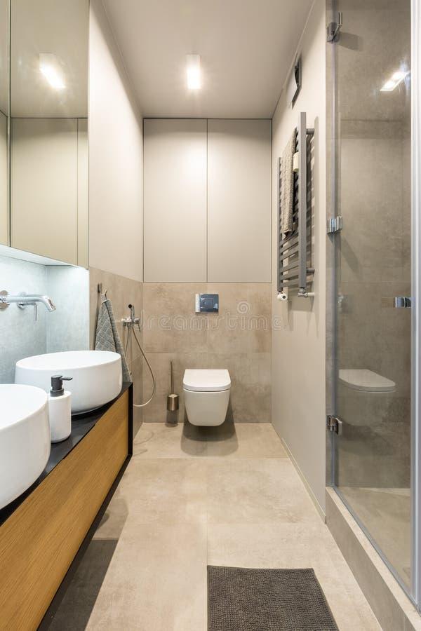 Άσπρη τουαλέτα κάτω από το φως στο σύγχρονο μπεζ εσωτερικό λουτρών με στοκ εικόνες με δικαίωμα ελεύθερης χρήσης