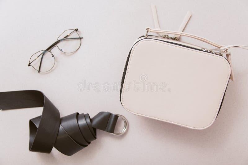 Άσπρη τσάντα, μαύρα ζώνη δέρματος και γυαλιά μόδας σε ένα μπεζ υπόβαθρο στοκ εικόνα