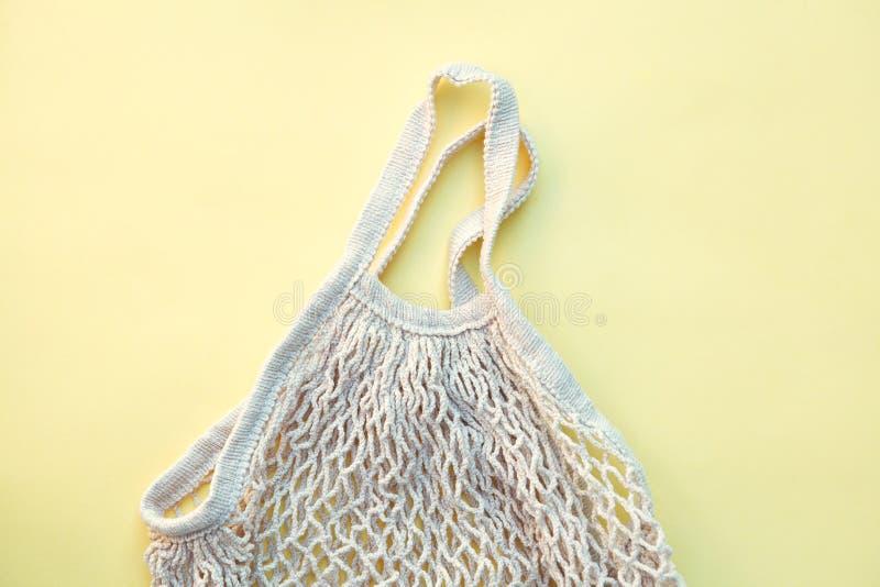 Άσπρη φιλική προς το περιβάλλον τσάντα σειράς που απομονώνεται στο κίτρινο υπόβαθρο, αρμόδια κατανάλωση στοκ φωτογραφία