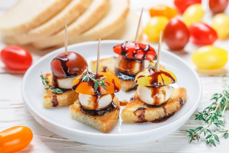 Άσπρη φρυγανιά ψωμιού με το κεράσι ντοματών, το τυρί μοτσαρελών, το θυμάρι και bal στοκ εικόνες