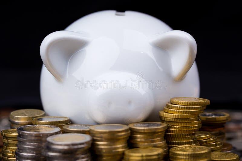 Άσπρη piggy τράπεζα πίσω από τα νομίσματα στη σκοτεινή ρύθμιση στοκ εικόνες με δικαίωμα ελεύθερης χρήσης