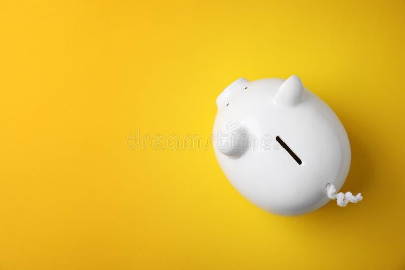 Άσπρη piggy τράπεζα στο υπόβαθρο χρώματος στοκ εικόνες