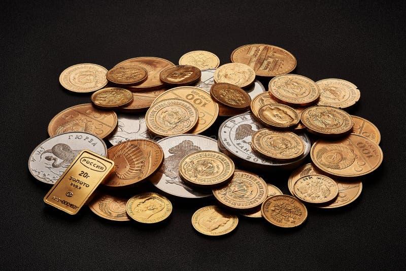 Άσπροι και κίτρινοι χρυσοί φραγμοί και νομίσματα που απομονώνονται στο μαύρο υπόβαθρο στοκ εικόνα