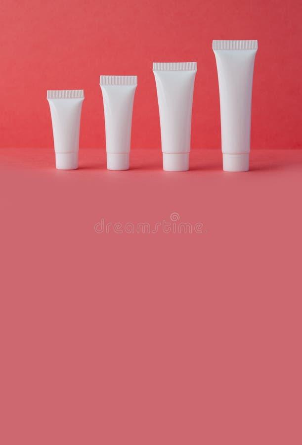 Άσπροι καλλυντικοί σωλήνες στο ρόδινο υπόβαθρο Κενά πλαστικά εμπορευματοκιβώτια, ρηχό βάθος του τομέα, διαστημική φωτογραφία αντι στοκ φωτογραφίες