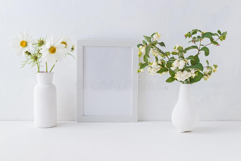 Άσπροι πλαίσιο και κλάδοι προτύπων με τα πράσινα φύλλα σε ένα βάζο στοκ εικόνες
