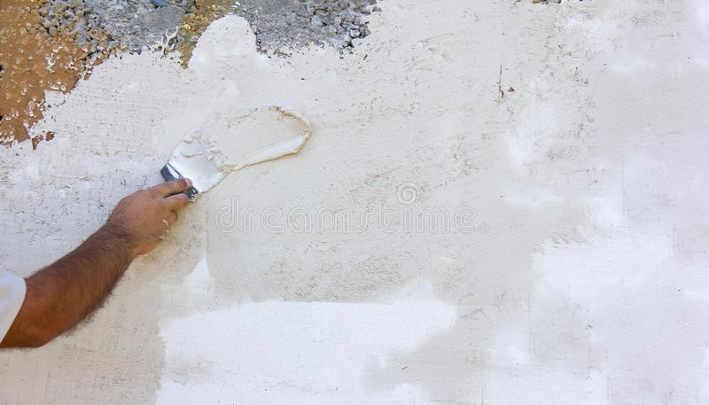 Άσπροι τραχιοί επικονιασμένοι τοίχοι σύστασης υποβάθρου και ένα αρσενικό χέρι με spatula στοκ φωτογραφία