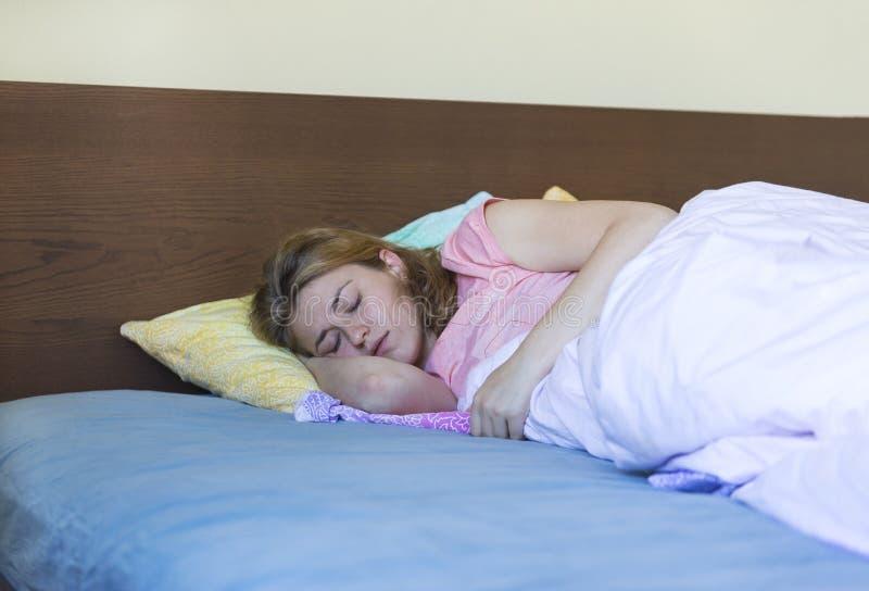 Άσπροι ύπνοι κοριτσιών στο κρεβάτι κάτω από ένα κάλυμμα στοκ εικόνες με δικαίωμα ελεύθερης χρήσης