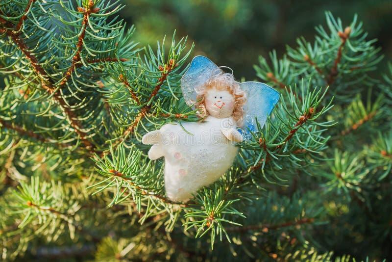 Άσπρος άγγελος, χειροποίητος, διακοσμήσεις στις πράσινες κομψές Χριστουγέννων στοκ εικόνες