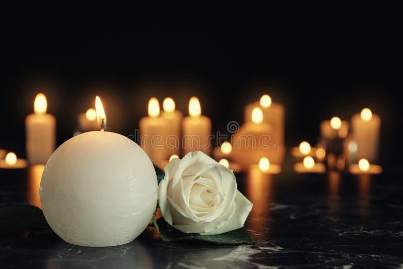 Άσπρος αυξήθηκε και καίγοντας κερί στον πίνακα στο σκοτάδι, διάστημα για το κείμενο στοκ φωτογραφία