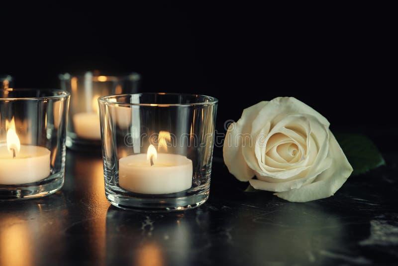 Άσπρος αυξήθηκε και καίγοντας κεριά στον πίνακα στο σκοτάδι στοκ εικόνα