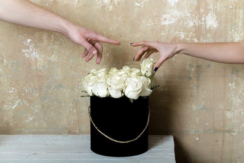 Άσπρος αυξήθηκε Ρομαντική ημερομηνία με τα λουλούδια Ανθοδέσμη των άσπρων τριαντάφυλλων και δύο χέρια του ευτυχούς ζεύγους Λουλού στοκ φωτογραφία