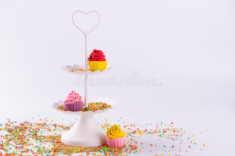 Άσπρος εξυπηρετώντας δίσκος δύο σειρών και μικροσκοπική πολύχρωμη ζάχαρη cupcakes στοκ φωτογραφία με δικαίωμα ελεύθερης χρήσης