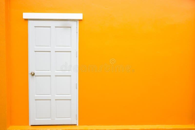 Άσπρος κλασικός τρύγος πορτών στον πορτοκαλή τοίχο χρώματος στοκ φωτογραφίες