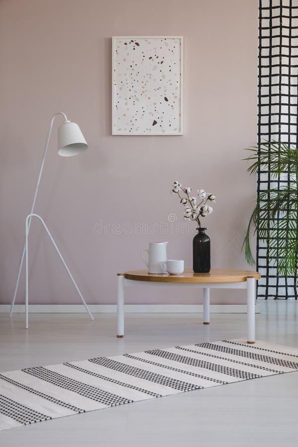 Άσπρος λαμπτήρας δίπλα στο ξύλινο τραπεζάκι σαλονιού με το λουλούδι βαμβακιού στο μαύρο βάζο, τα φλυτζάνια καφέ και την κανάτα στοκ φωτογραφία με δικαίωμα ελεύθερης χρήσης