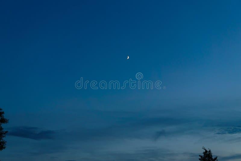 Άσπρος μήνας ενάντια στο σκοτεινό ουρανό στο σούρουπο στοκ φωτογραφία