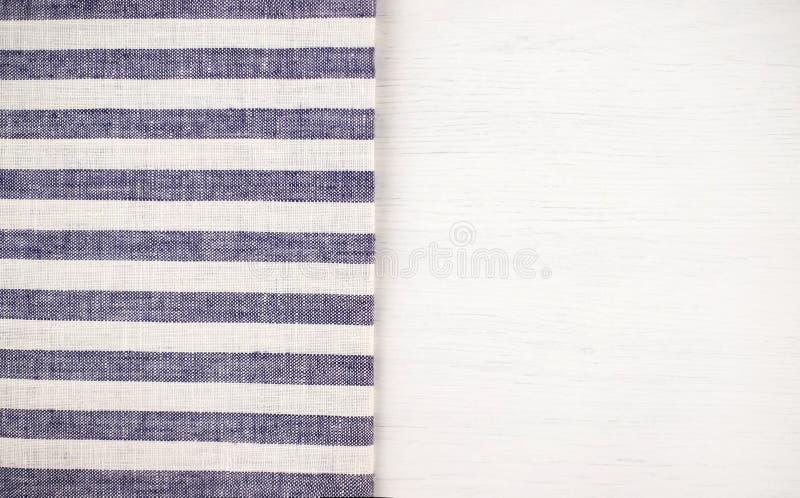 Άσπρος ξύλινος πίνακας με ένα μπλε ριγωτό τραπεζομάντιλο στοκ εικόνα