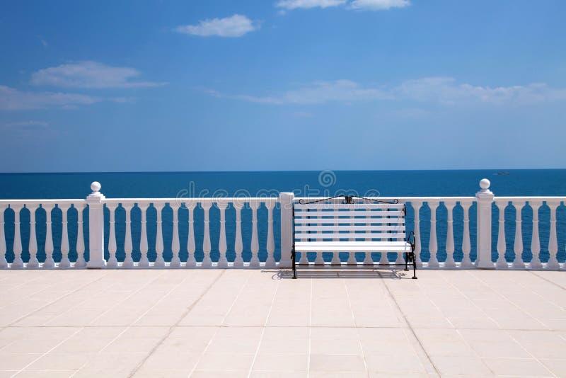 Άσπρος πάγκος, κιγκλίδωμα και κενό πεζούλι που αγνοούν τη θάλασσα στοκ φωτογραφία