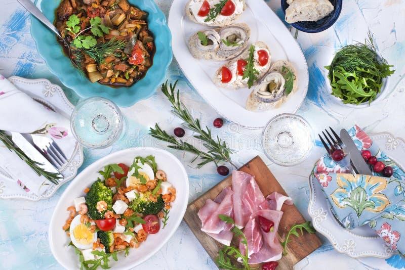 Άσπρος πίνακας με τα διαφορετικές τρόφιμα, τις σαλάτες και τα πρόχειρα φαγητά, τα πιάτα και τις πετσέτες στοκ εικόνα
