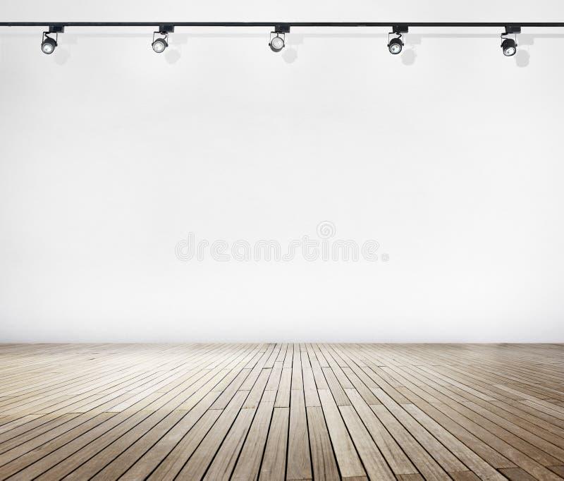 Άσπρος τοίχος και ξύλινο πάτωμα με τα επίκεντρα στοκ εικόνες