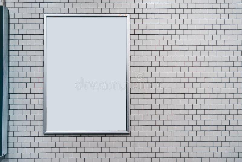 Άσπρος τοίχος κεραμιδιών με τον κενό πίνακα Χλεύη επάνω με το copyspace στοκ φωτογραφία