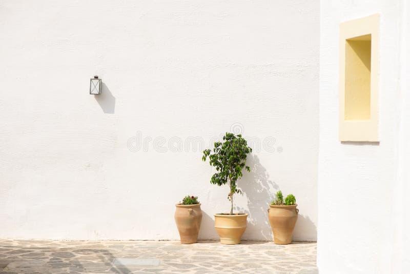 Άσπρος τοίχος με ηλεκτρικό λαμπτήρα και τρία δοχεία λουλουδιών στοκ εικόνες