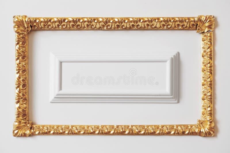 Άσπρος τοίχος με το χαρασμένο χρυσό πλαίσιο στοκ φωτογραφίες