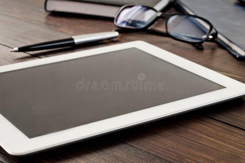 Άσπρος υπολογιστής ταμπλετών στην ξύλινη επιτραπέζια κινηματογράφηση σε πρώτο πλάνο γραφείων στοκ εικόνα με δικαίωμα ελεύθερης χρήσης