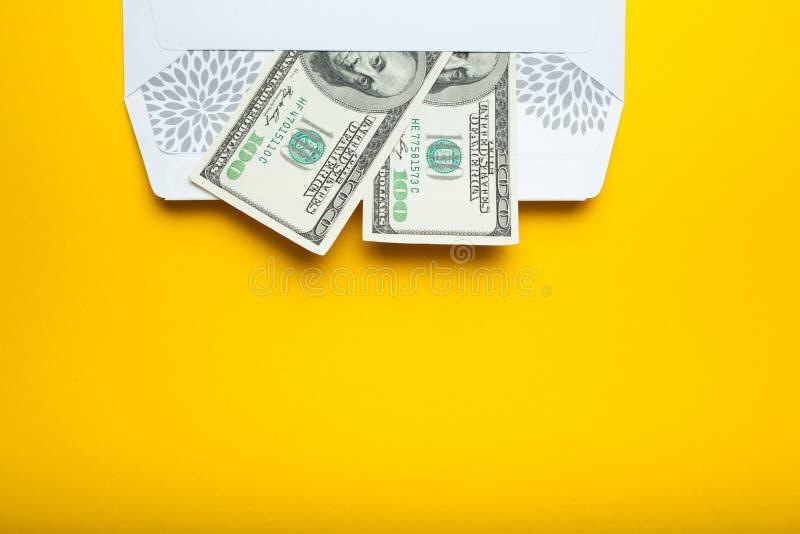 Άσπρος φάκελος με τα δολάρια σε ένα κίτρινο υπόβαθρο, κενό διάστημα για το κείμενο στοκ φωτογραφία