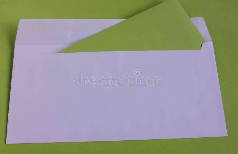 Άσπρος φάκελος σε ένα πράσινο υπόβαθρο στοκ εικόνα