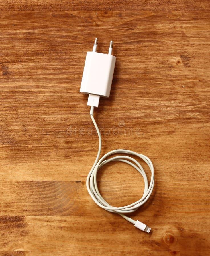 Άσπρος φορτιστής smartphone πέρα από τον ξύλινο πίνακα στοκ φωτογραφία με δικαίωμα ελεύθερης χρήσης