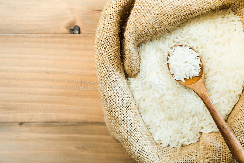 Άσπρο ακατέργαστο ταϊλανδικό jasmine ρύζι στο ξύλινο κουτάλι gunny στο σάκο στην ξύλινη επιτραπέζια σύσταση στοκ εικόνες