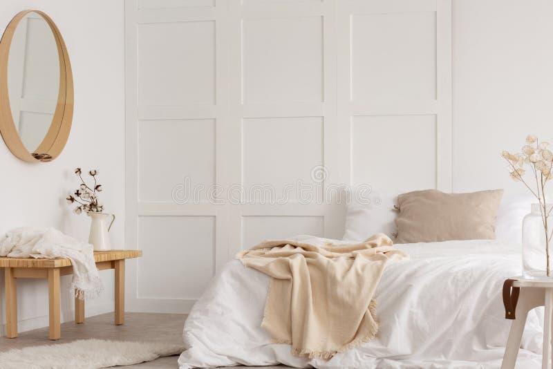 Άσπρο απλό σχέδιο κρεβατοκάμαρων με τον καθρέφτη και το κρεβάτι με τα άσπρα φύλλα στοκ εικόνα