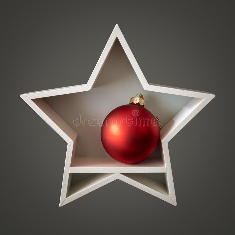 Άσπρο αστέρι διακοσμήσεων Χριστουγέννων με την κόκκινη σφαίρα γυαλιού μέσα στοκ εικόνες
