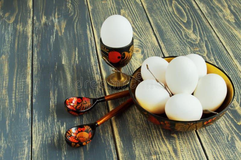 Άσπρο αυγό στην ξύλινη στάση, αυγά στο ξύλινο ζωηρόχρωμο πιάτο και ξύλινα χρωματισμένα κουτάλια στο τραχύ παλαιό ξύλινο υπόβαθρο  στοκ εικόνες