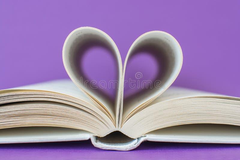 Άσπρο βιβλίο με τις σελίδες που διαμορφώνουν μια καρδιά που απομονώνεται στο πορφυρό υπόβαθρο Αγαπώ την έννοια στοκ φωτογραφία με δικαίωμα ελεύθερης χρήσης