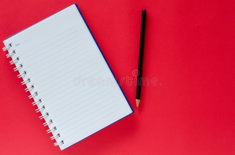 Άσπρο βιβλίο σημειώσεων και μαύρο μολύβι στο υπόβαθρο κόκκινου χρώματος με ομο στοκ εικόνα