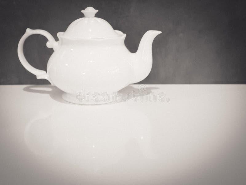 Άσπρο βρετανικό δοχείο τσαγιού πορσελάνης στον άσπρο καλό τόνο επιτραπέζιου γκρίζο υποβάθρου στοκ εικόνες