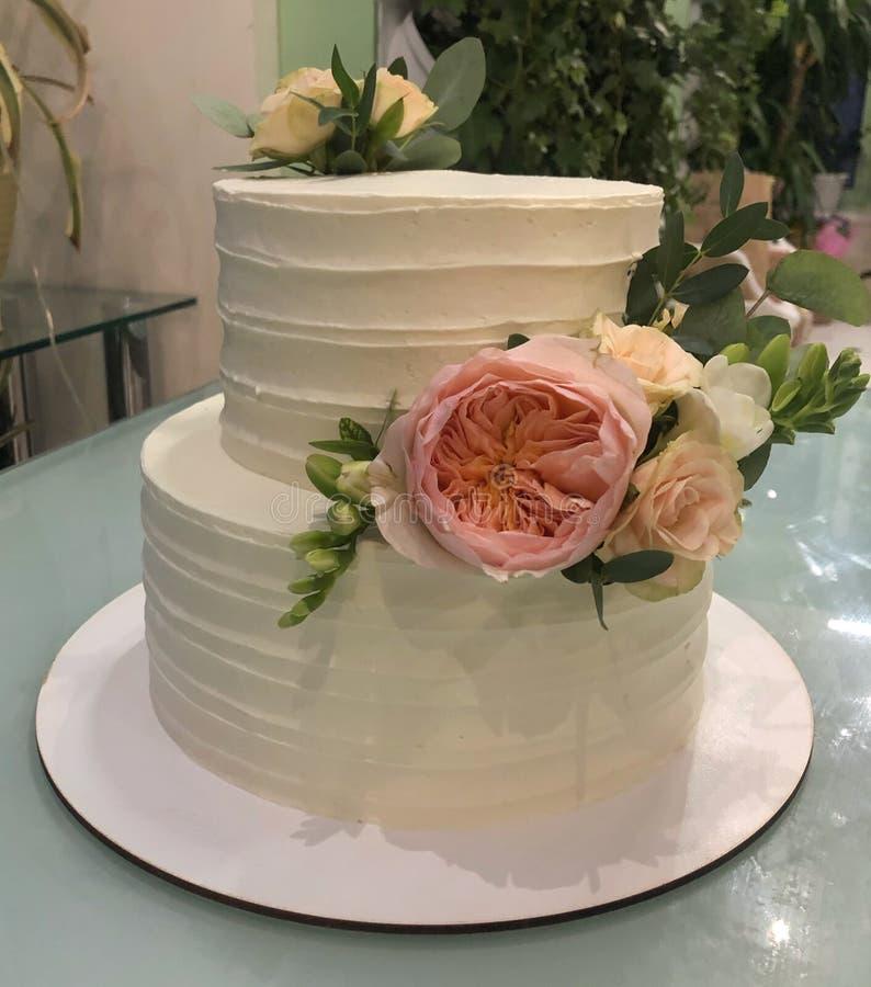 άσπρο γαμήλιο κέικ με τα λουλούδια στοκ εικόνα