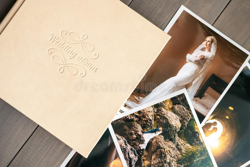 Άσπρο γαμήλιο λεύκωμα δέρματος και τυπωμένες φωτογραφίες με τη νύφη και το νεόνυμφο στοκ εικόνες