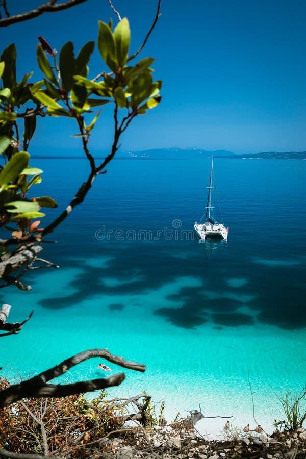 Άσπρο γιοτ καταμαράν στην άγκυρα στη σαφή κυανή επιφάνεια με το σκοτεινό σχέδιο στην ήρεμη μπλε λιμνοθάλασσα Unrecognizable τουρί στοκ φωτογραφίες με δικαίωμα ελεύθερης χρήσης