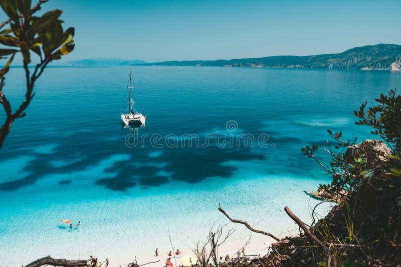 Άσπρο γιοτ καταμαράν στην άγκυρα στη σαφή κυανή επιφάνεια νερού στην ήρεμη μπλε λιμνοθάλασσα Unrecognizable ελεύθερος χρόνος τουρ στοκ εικόνα με δικαίωμα ελεύθερης χρήσης
