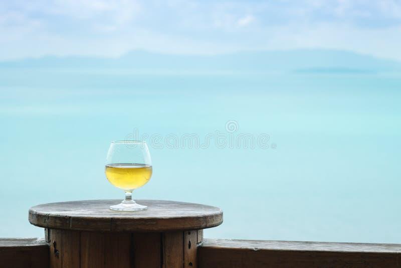 Άσπρο γυαλί κρασιού κινηματογραφήσεων σε πρώτο πλάνο στον πίνακα στο πεζούλι στο υπόβαθρο άποψης θάλασσας στοκ φωτογραφία