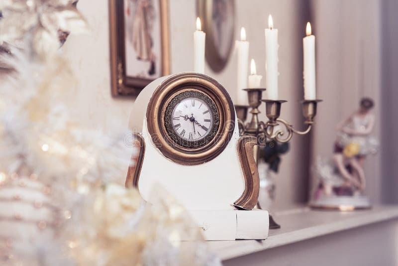 Άσπρο εκλεκτής ποιότητας ρολόι στο καίγοντας υπόβαθρο κεριών στοκ εικόνα
