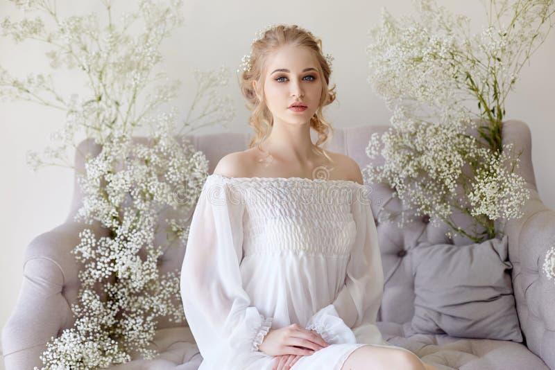 Άσπρο ελαφρύ φόρεμα κοριτσιών και σγουρή τρίχα, πορτρέτο της γυναίκας με τα λουλούδια στο σπίτι κοντά στο παράθυρο, αγνότητα και  στοκ φωτογραφίες
