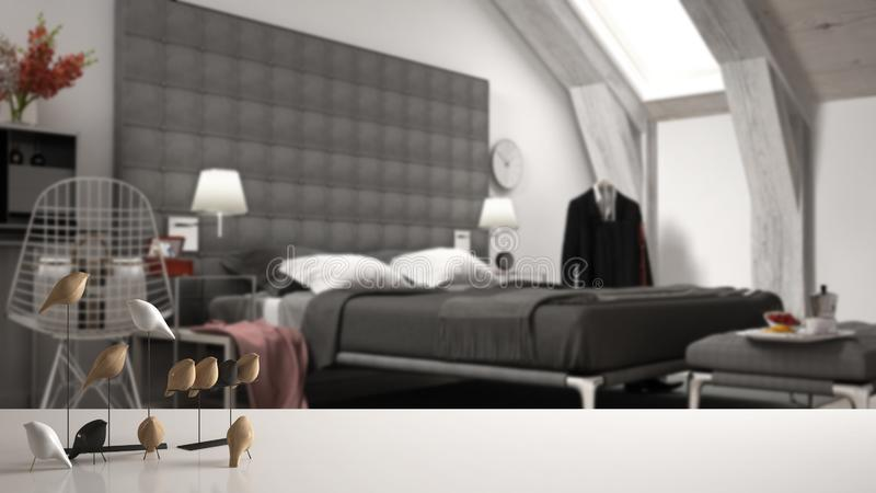 Άσπρο επιτραπέζια κορυφή ή ράφι με τη minimalistic διακόσμηση πουλιών, birdie μπιχλιμπίδι πέρα από τη θολωμένη σύγχρονη κρεβατοκά απεικόνιση αποθεμάτων