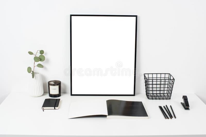 Άσπρο επιτραπέζιο διάστημα εργασίας γραφείων εσωτερικό, μοντέρνο με την αφίσα artw στοκ φωτογραφίες