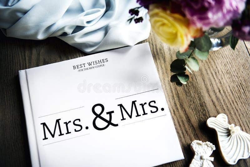 Άσπρο λεσβιακό βιβλίο γαμήλιων φιλοξενουμένων που τοποθετούνται στον ξύλινο πίνακα στοκ εικόνες
