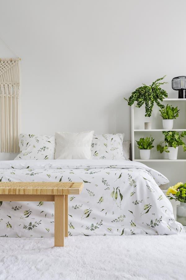 Άσπρο εσωτερικό κρεβατοκάμαρων με τις φρέσκες εγκαταστάσεις στο ράφι, floral φύλλα στο διπλό κρεβάτι, τάπητας στο πάτωμα στοκ εικόνες